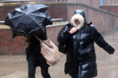 Two women struggle in rain and strong winds near St Paul's Cathedral on January 7 2014 in London England Over 100 areas of the UK have been warned by...
