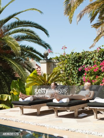 Two Women Sun Bathing In Lounge Chairs By A Pool Stock