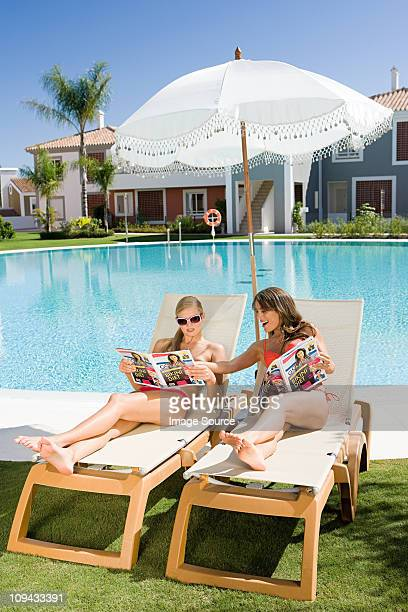 Two women sunbathing on sunloungers reading magazines