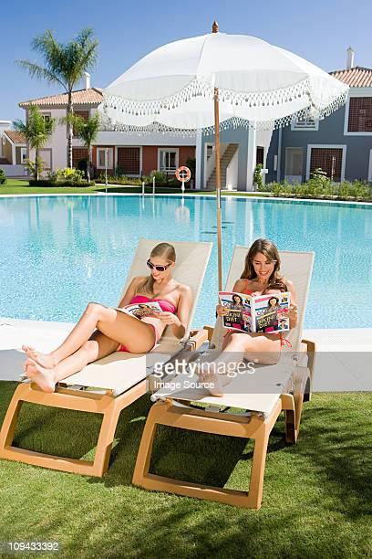 Zwei Frauen Sonnenbaden auf Sonnenliegen Lesung Zeitschriften