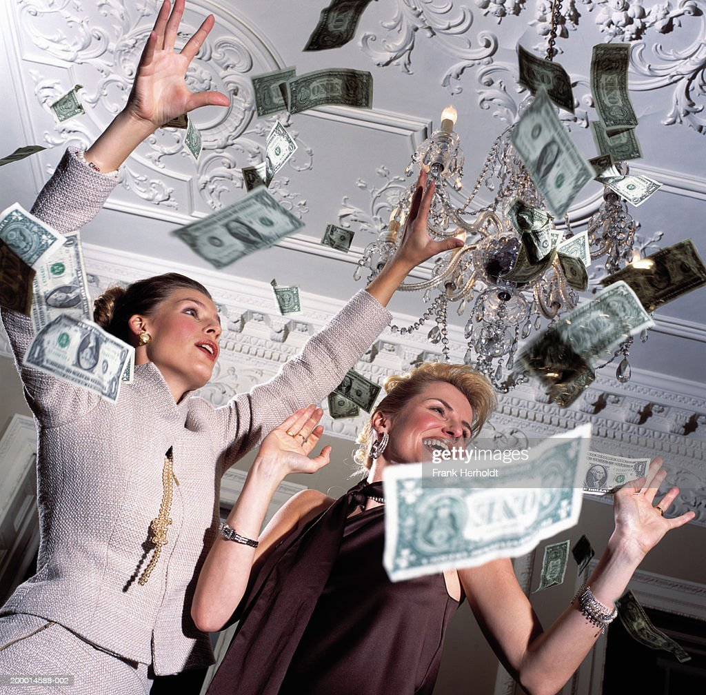 Two women surrounded by falling banknotes, low angle view : Stock Photo
