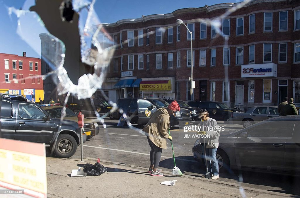 Two women sweeping up the streets are reflected in the broken window of a check cashing store in Baltimore Maryland April 28 2015 Riot police and...