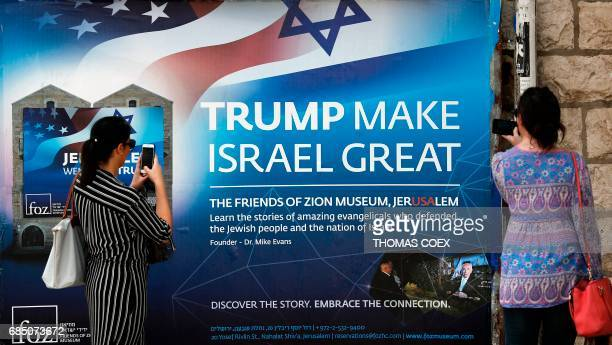 Two women take a picture of a poster welcoming and supporting US President Donald Trump in downtown Jerusalem on May 19 three days ahead of a two day...