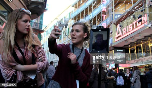 Two women take a selfie as they wait with others outside the Ariston Theatre in Sanremo on February 6 before the start of the annual music festival...