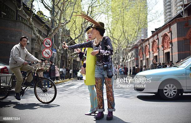 Two women take a selfie before a fashion show on the streets during the Shanghai Fashion Week in Shanghai on April 8 2015 AFP PHOTO / JOHANNES EISELE...