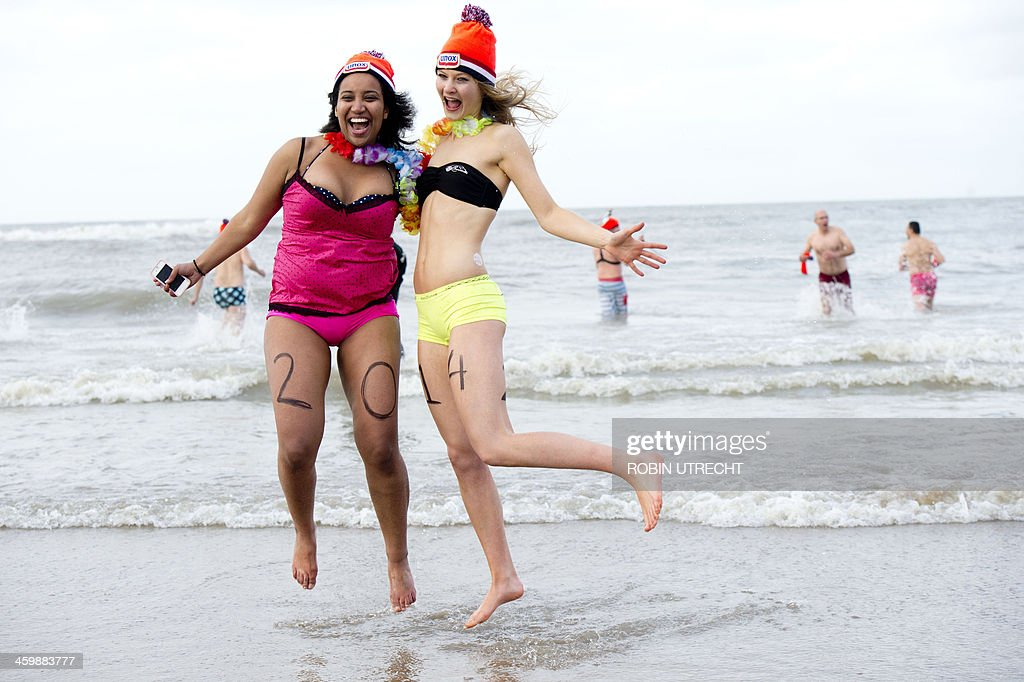 Two women take part in the traditional sea bathing to mark the start of the new year on January 1, 2014 in Scheveningen. AFP PHOTO/ANP/ ROBIN UTRECHT netherlands out