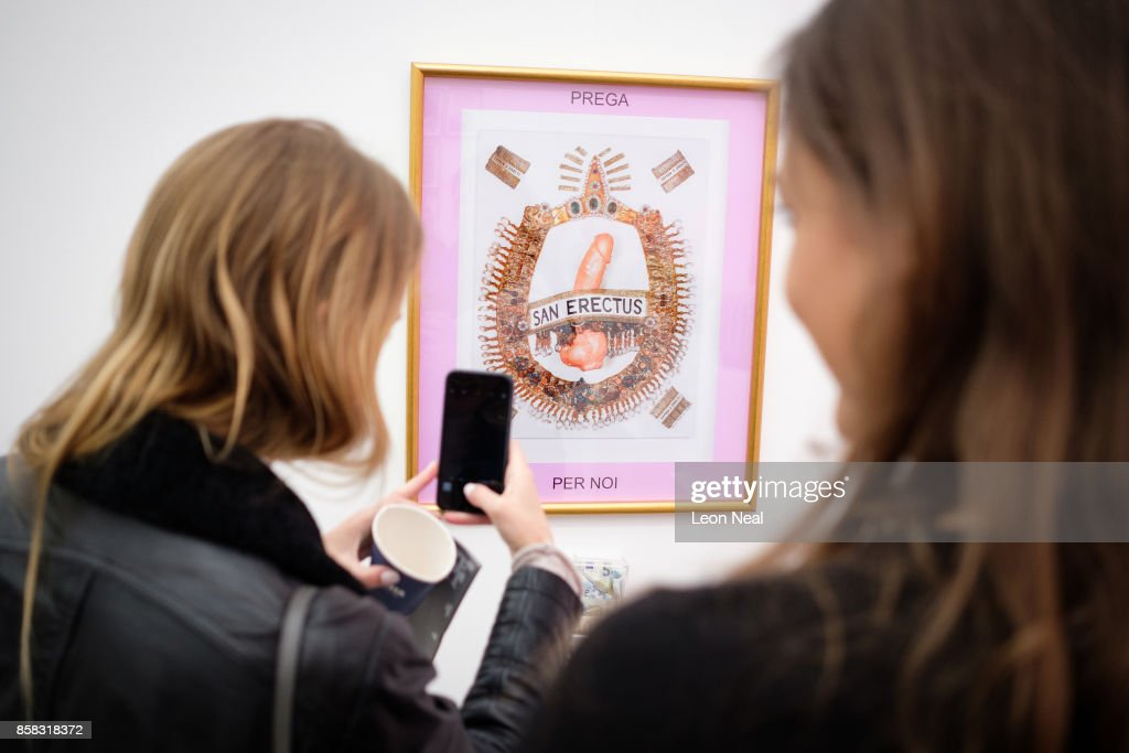 Two women take photographs of 'San Erectus Prega Per Noi' by Renate Bertlmann at the Frieze Art Fair on October 6, 2017 in London, England. The annual event sees galleries showcase work by thousands of artists from around the world. The Frieze Art Fair runs from 5-8 October, 2017.