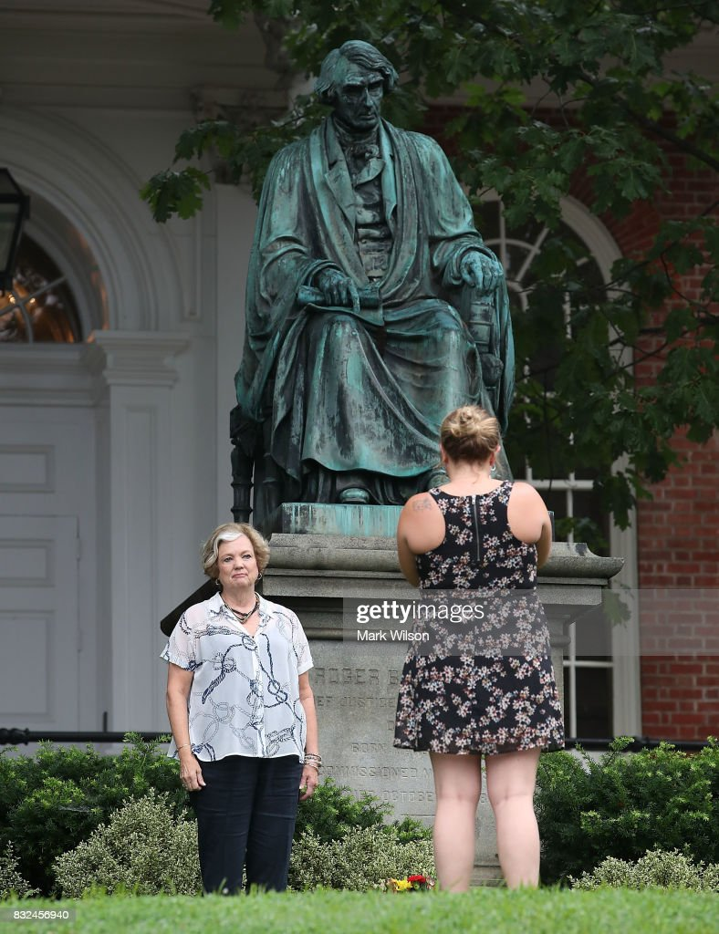 Two women take pictures in front of the statue of US Supreme Court Chief Justice Roger Brooke Taney that sits in front of the Maryland State House, on August 16, 2017 in Annapolis, Maryland. Maryland Governor Larry Hogan has called for the removal of the statue. Taney was the author of the Dred Scott decision.