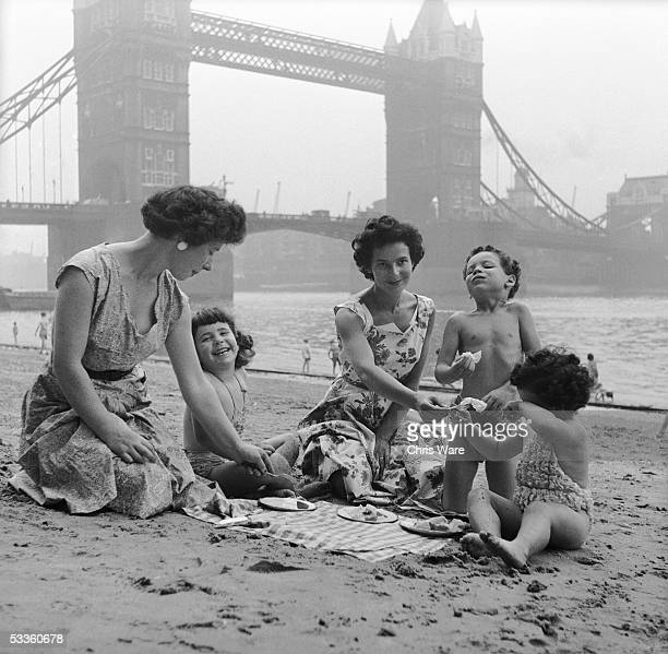 Two women take their children for a picnic on Tower Beach an artificial beach near Tower Bridge on the River Thames London 31st August 1955