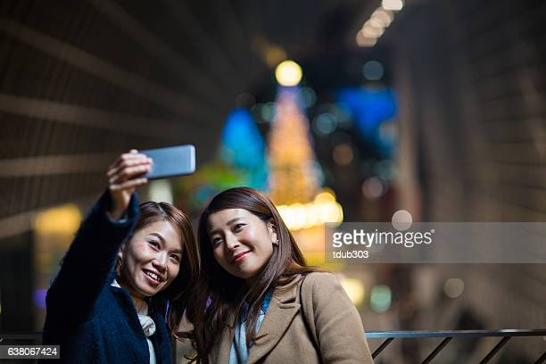 Two women taking a selfie at night in the city