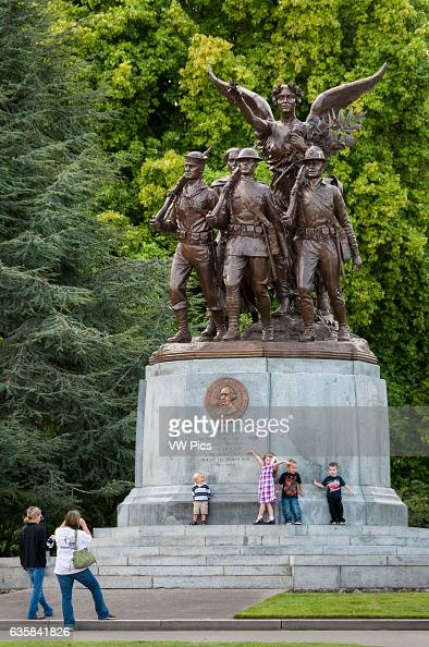 Two women taking pictures of kids at World War I memorial at state capitol Olympia Washington