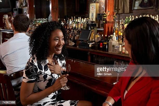 Two women talking at bar