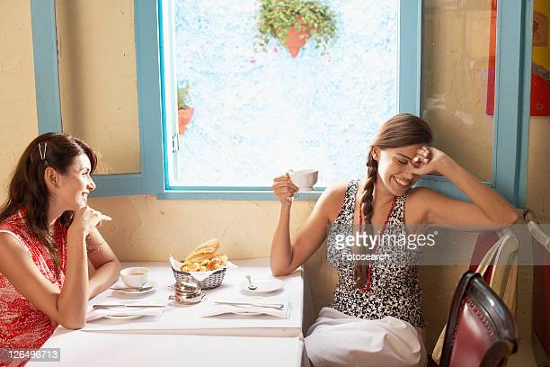 Two women talking at dining table in restaurant