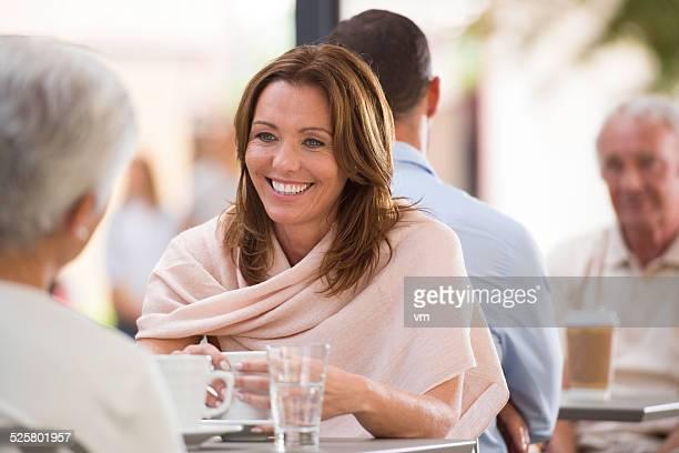Duas mulheres de falar em um Café Esplanada