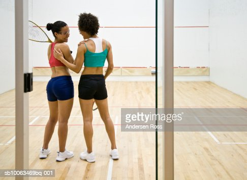 Two women talking in indoor racquetball court, rear view