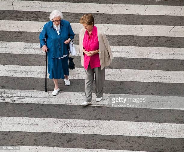 Two women talking while walking at a zebra crossing