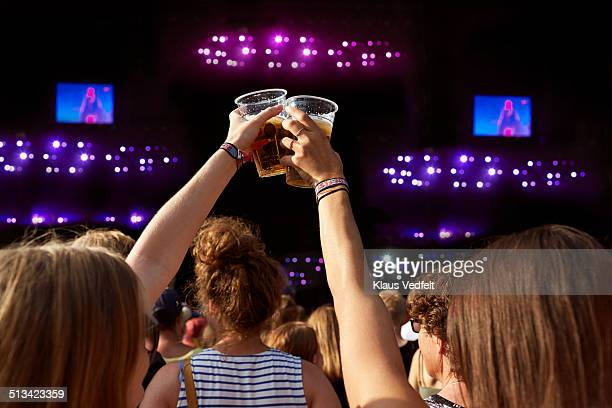 Two women toasting in beer at concert