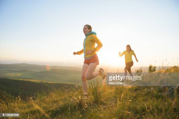Two women trail running outdoor on a green field
