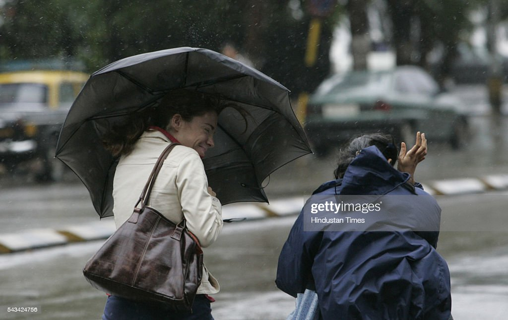 Two women tries to get hold their umbrella at Nariman point on August 1, 2005 in Mumbai, India. in Mumbai, India. as weather department predicted storm and heavy rains for next 24 hours.