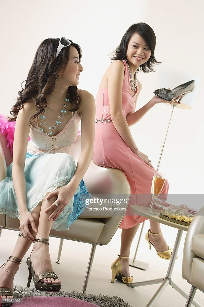 Two women trying on shoes : Stock Photo