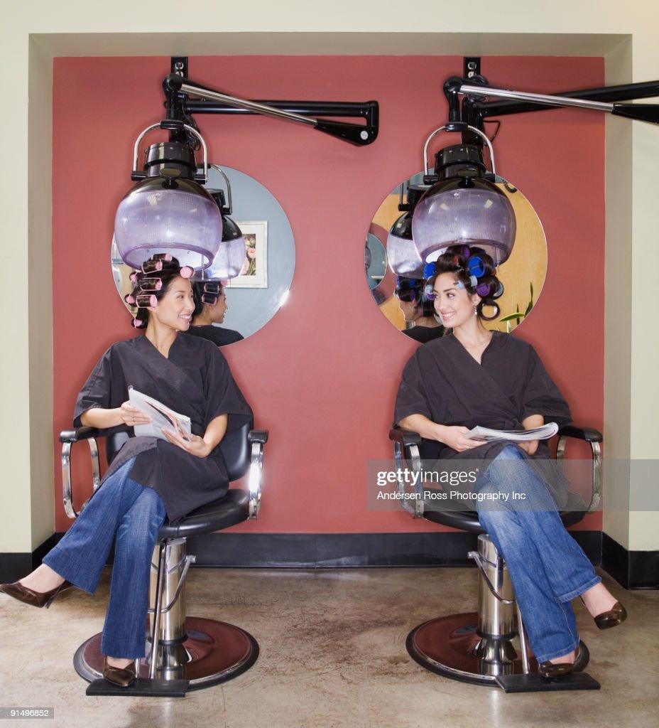 Two women under hair dryers in salon