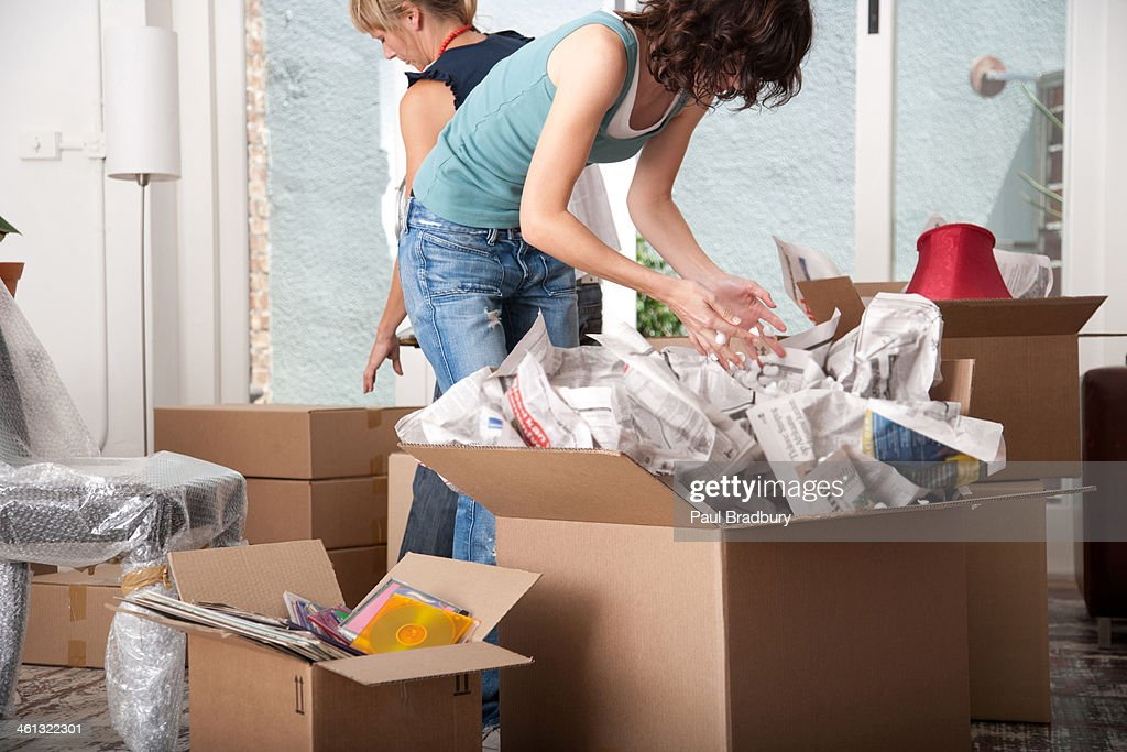 Two women unpacking cardboard boxes