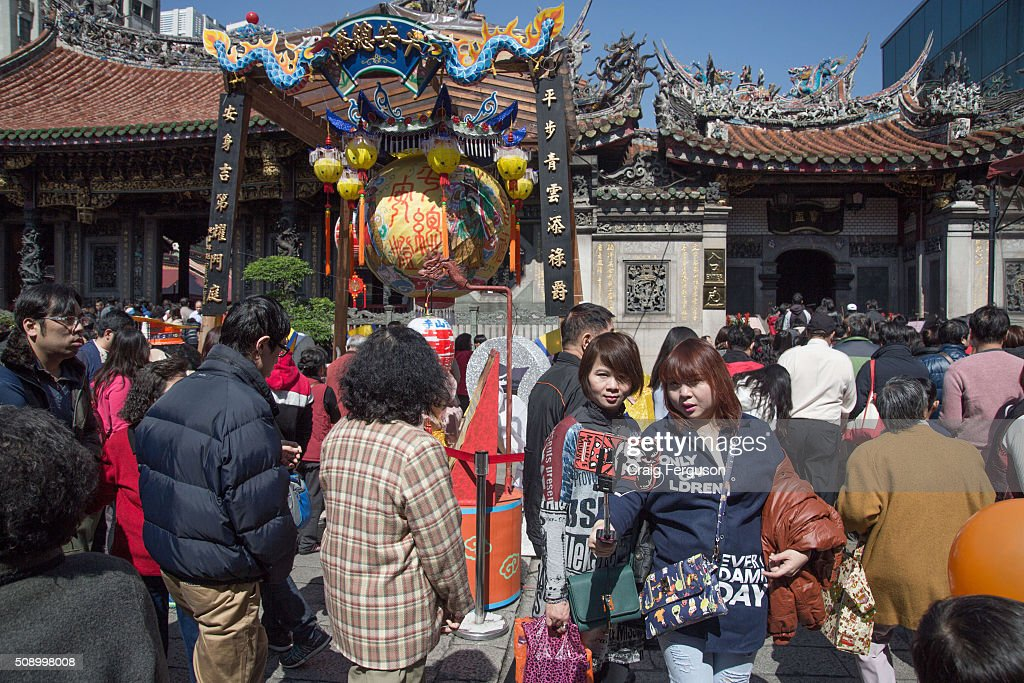 Two women use a selfie stick to take a selfie outside Longshan Temple. On the first day of the Chinese lunar year it is traditional to visit temples to light incense and pray for a prosperous year. Thousands come to Longshan Temple, one of the oldest and most important in Taipei every year.