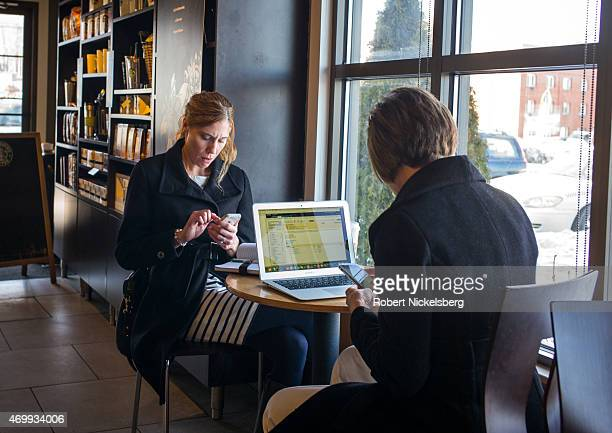 Two women use their iPhones and a computer February 11 2015 while sitting in a Starbucks Coffee shop in Milford Connecticut