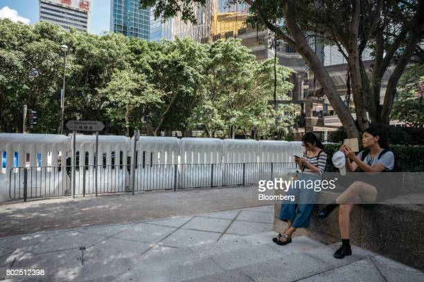 Two women use their smartphones in front of water barricades near the Hong Kong Convention and Exhibition Center ahead of Chinese President Xi...