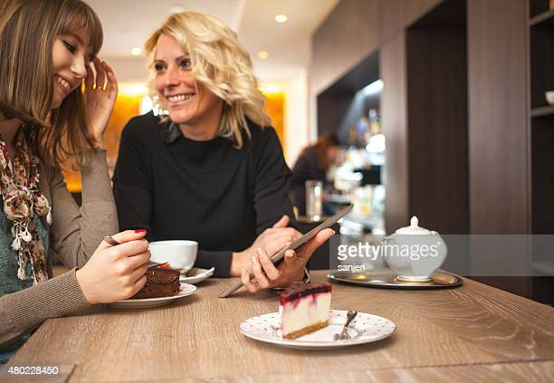 Two women using digital tablet at the coffee shop