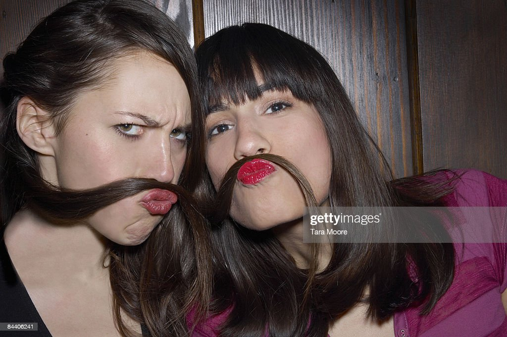 two women using hair as moustaches : Stock Photo