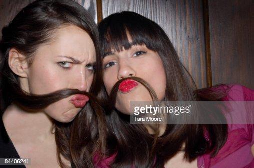 two women using hair as moustaches : Stock Photo