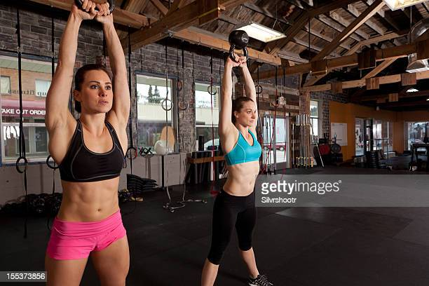 Two women using kettle bells