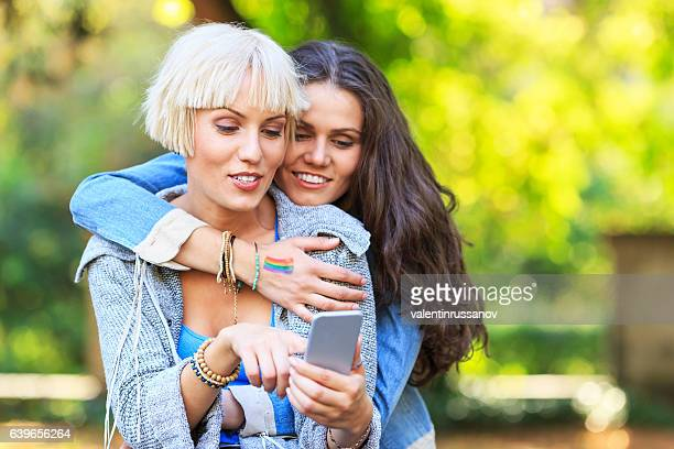 Two women using smart phone in park