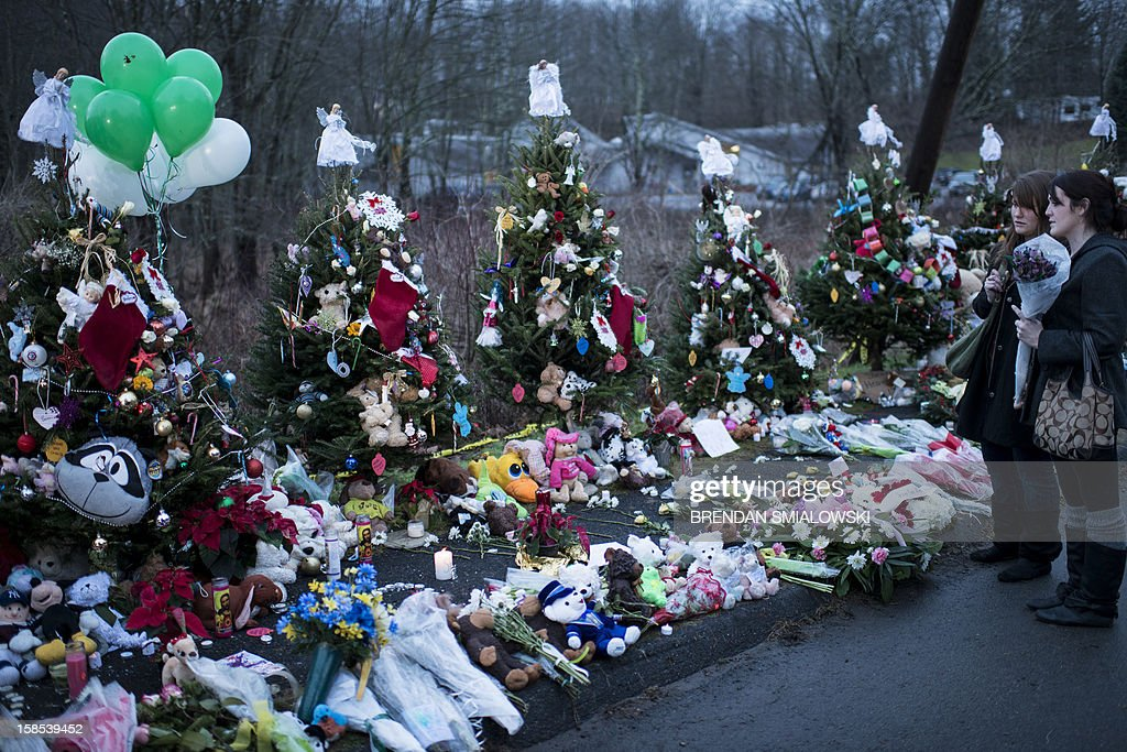 Two women visit a makeshift memorial near the entrance to the grounds of Sandy Hook Elementary School on December 18, 2012 in Newtown, Connecticut. Students in Newtown, excluding Sandy Hook Elementary School, return to school for the first time since last Friday's shooting at Sandy Hook which took the live of 20 students and 6 adults. AFP PHOTO/Brendan SMIALOWSKI