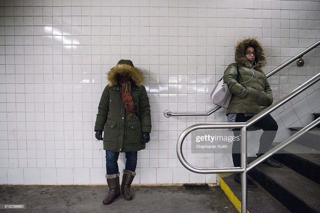 Two women wait for a subway train during an arctic chill that brought frigid temperatures on February 14, 2016 in the Brooklyn borough of New York City. The city broke a 100-year record February 14, as emputures dropped minus 1 degree Fahrenheit.