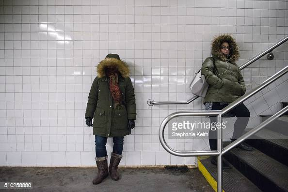 Two women wait for a subway train during an arctic chill that brought frigid temperatures on February 14 2016 in the Brooklyn borough of New York...