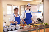 Two women waiting to serve lunch in a school cafeteria