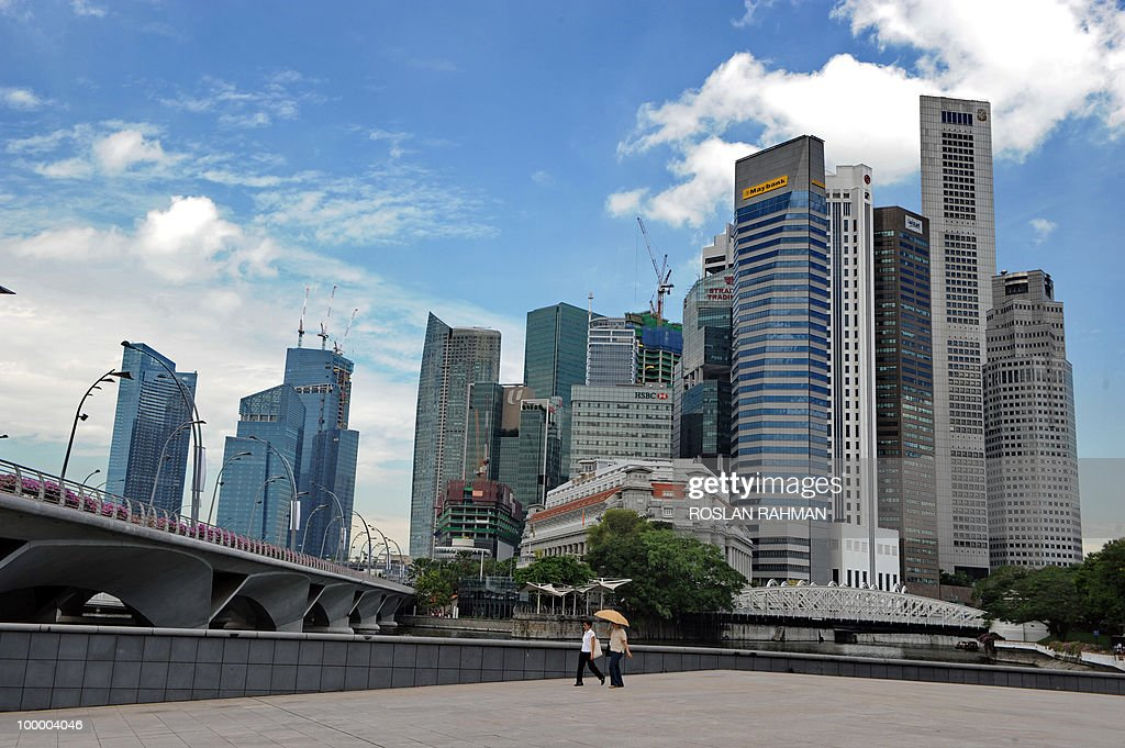 Two women walk along the walkway past the financial district in Singapore on May 20, 2010. Singapore's economy grew by a better-than-expected 15.5 percent year on year in the first quarter, spurred mainly by strong global demand for electronics, official data showed.