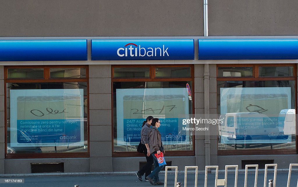 Two women walk in front of a Citi Bank in the city centre on April 15, 2013 in Timisoara, Romania. Romania has abandoned a target deadline of 2015 to switch to the single European currency and will now submit to the European Commission a programme on progress towards the adoption of the Euro, which for the first time will not have a target date.