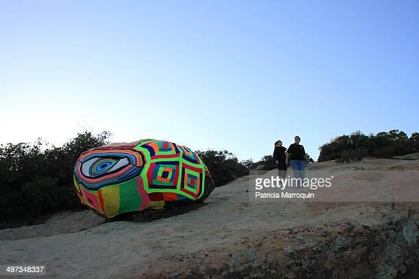 Two women walk near a yarn bomb at Lizard's Mouth Santa Barbara California
