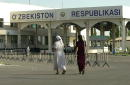Two women walk near an Uzbek border crossing that uses radiation detectors enlisted to control smuggling of nuclear materials from former Soviet...