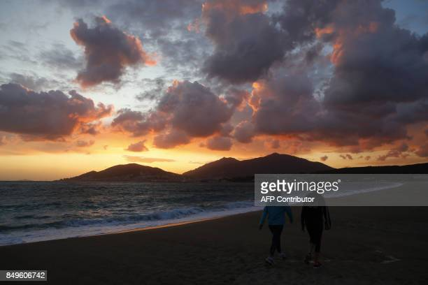 Two women walk on the Ricanto beach at sunset as Ajaccio is seen in the background on September 19 2017 on the French Mediterranean Island of Corsica...