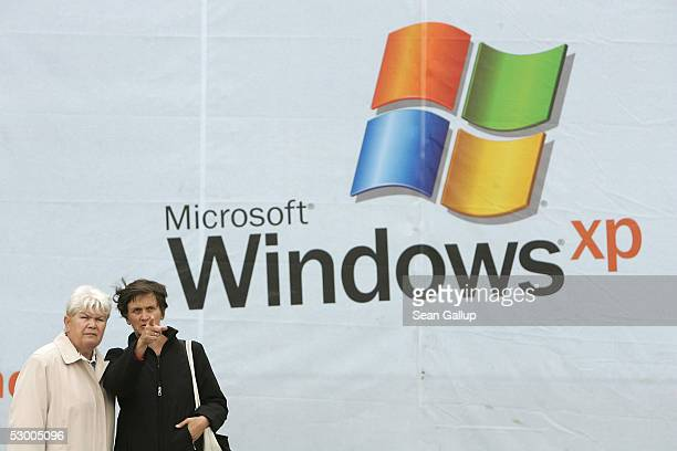 Two women walk past a billboard advertising the Microsoft Windows XP operating system June 1 2005 in Berlin Germany Microsoft is locked in a legal...