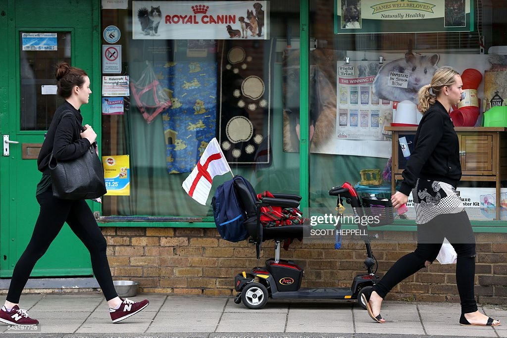 Two women walk past a mobility scooter, parked outside a shop, with a St Georges flag attached in Redcar, north east England on June 27, 2016 Britain's historic decision to leave the 28-nation bloc has sent shockwaves through the political and economic fabric of the nation. It has also fuelled fears of a break-up of the United Kingdom with Scotland eyeing a new independence poll, and created turmoil in the opposition Labour party where leader Jeremy Corbyn is battling an all-out revolt. / AFP / Scott Heppell