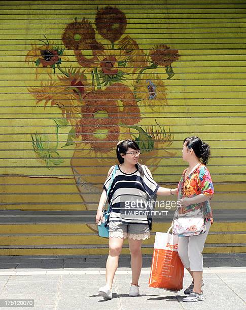 Two women walk past a set of stairs featuring a fivemetrehigh reproduction of Vincent van Gogh's signature painting 'Sunflowers' exhibited at the...
