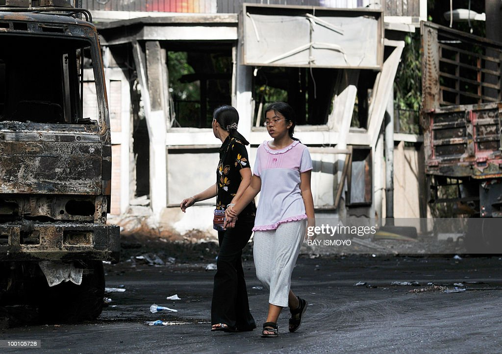 Two women walk past burnt trucks and a police post in downtown Bangkok on May 21, 2010. Thailand picked up the pieces after violence and mayhem triggered by a crackdown on anti-government protests, as the focus swung to recovery and reconciliation in a divided nation. AFP PHOTO / Bay ISMOYO