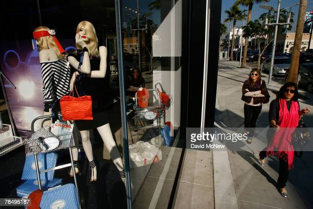 Two women walk past businesses that cater to highend luxury item consumers along Rodeo Drive on December 14 2007 in Beverly Hills California In the...