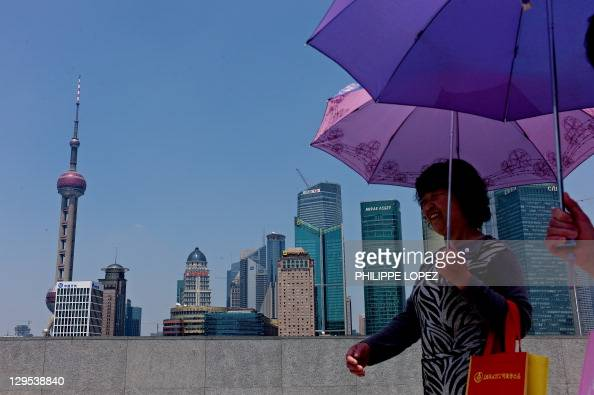 Two women walk past the skyline of Shanghai's financial district on June 2 2010 Chinese shares fell 161 percent in afternoon trading led by falls in...