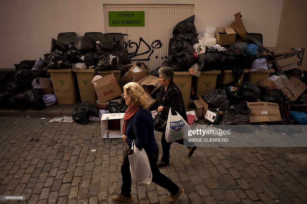 Two women walk past uncollected rubbish in a street of Sevilla on February 4, 2013. Rubbish collectors have been on strike in the municipality of Sevilla to protest against the austerity cuts imposed by the town hall. AFP PHOTO/ JORGE GUERRERO